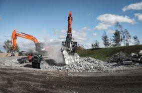 Fachbesucher erleben mineralische Aufbereitung mit den richtigenAnbaugeräten unter Anweisung.