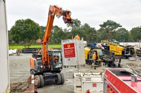 Am Haken hantiert der Mobilbagger mit Kraftstofftanks über das Baustellenfeld.