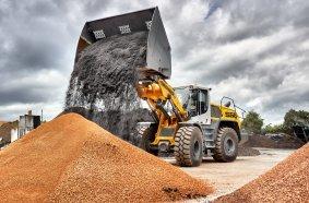 Ein L 556 XPower® mit Industrie-Kinematik und Hochkippschaufel verlädt Erde und Substrate.