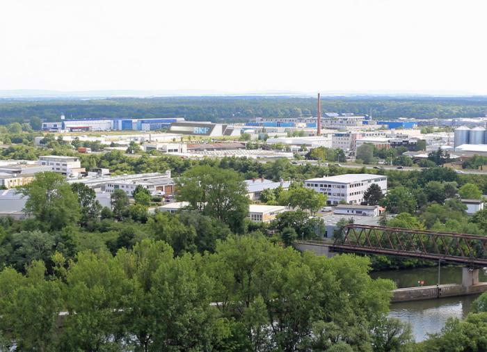 """Fotomontierter Blick vom SKF Hochhaus in Richtung """"Werk 3"""", wo das leistungsfähigste Großlager-Prüfzentrum der Welt im Jahr 2017 seinen Betrieb aufnehmen soll (Quelle rechtes Bild: nps tchoban voss)."""