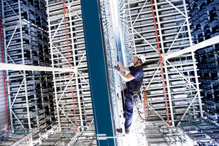 Techniker klettert mit seiner Sicherheitsausrüstung den Mast hoch