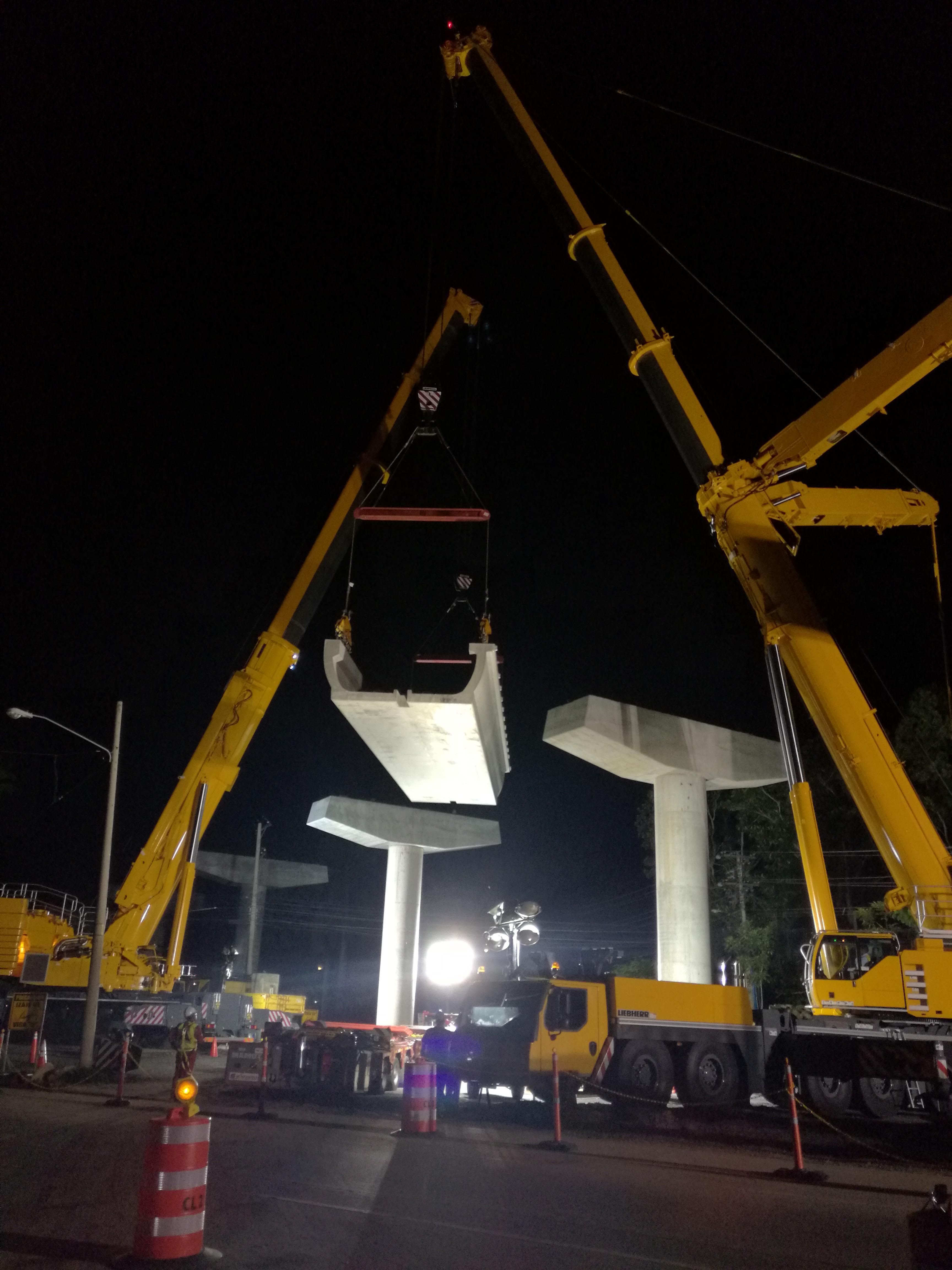 Hoisting a U-shaped beam onto the supports.