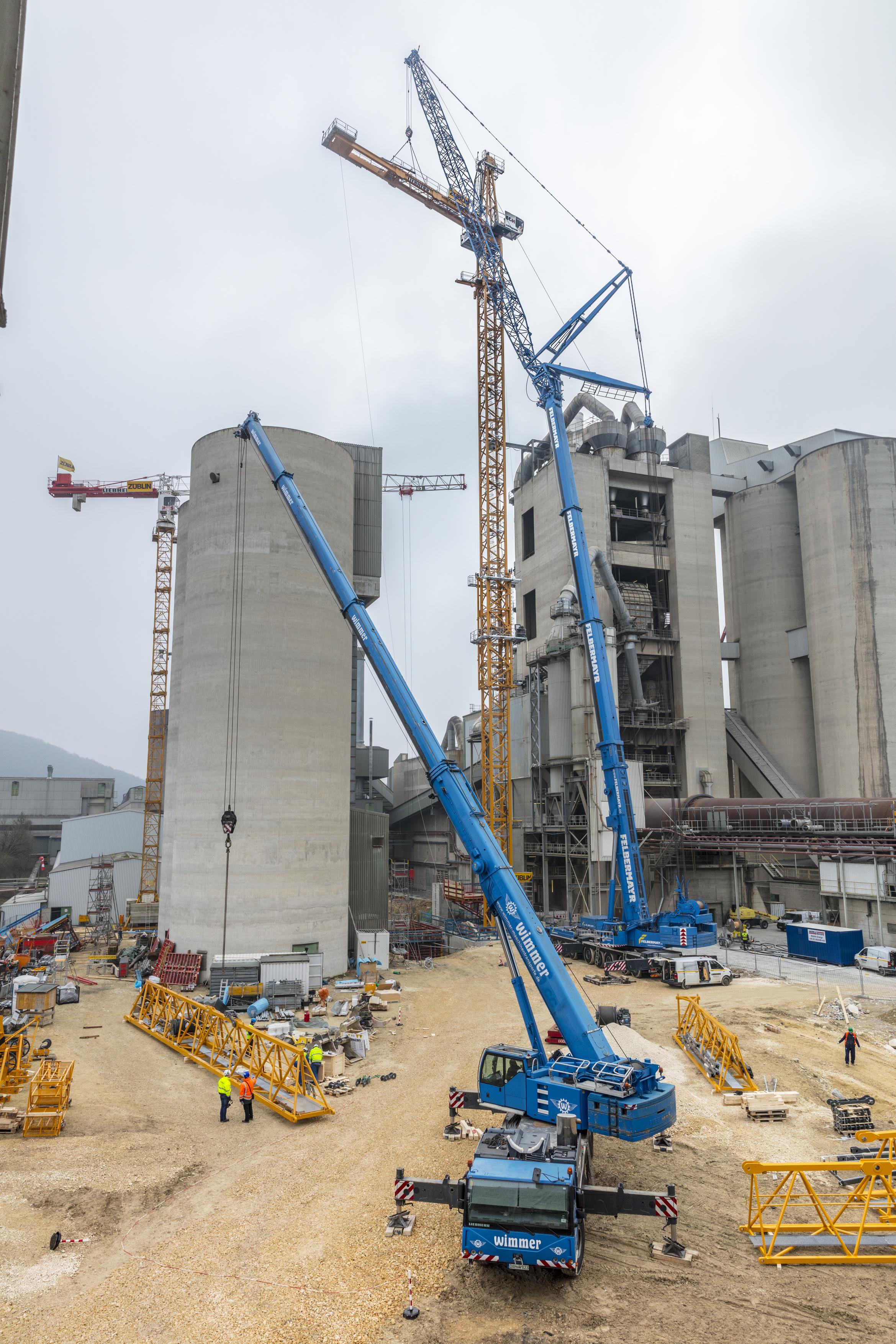 Two Liebherr mobile cranes assemble a Liebherr 1000 EC-H 50 Litronic tower crane.