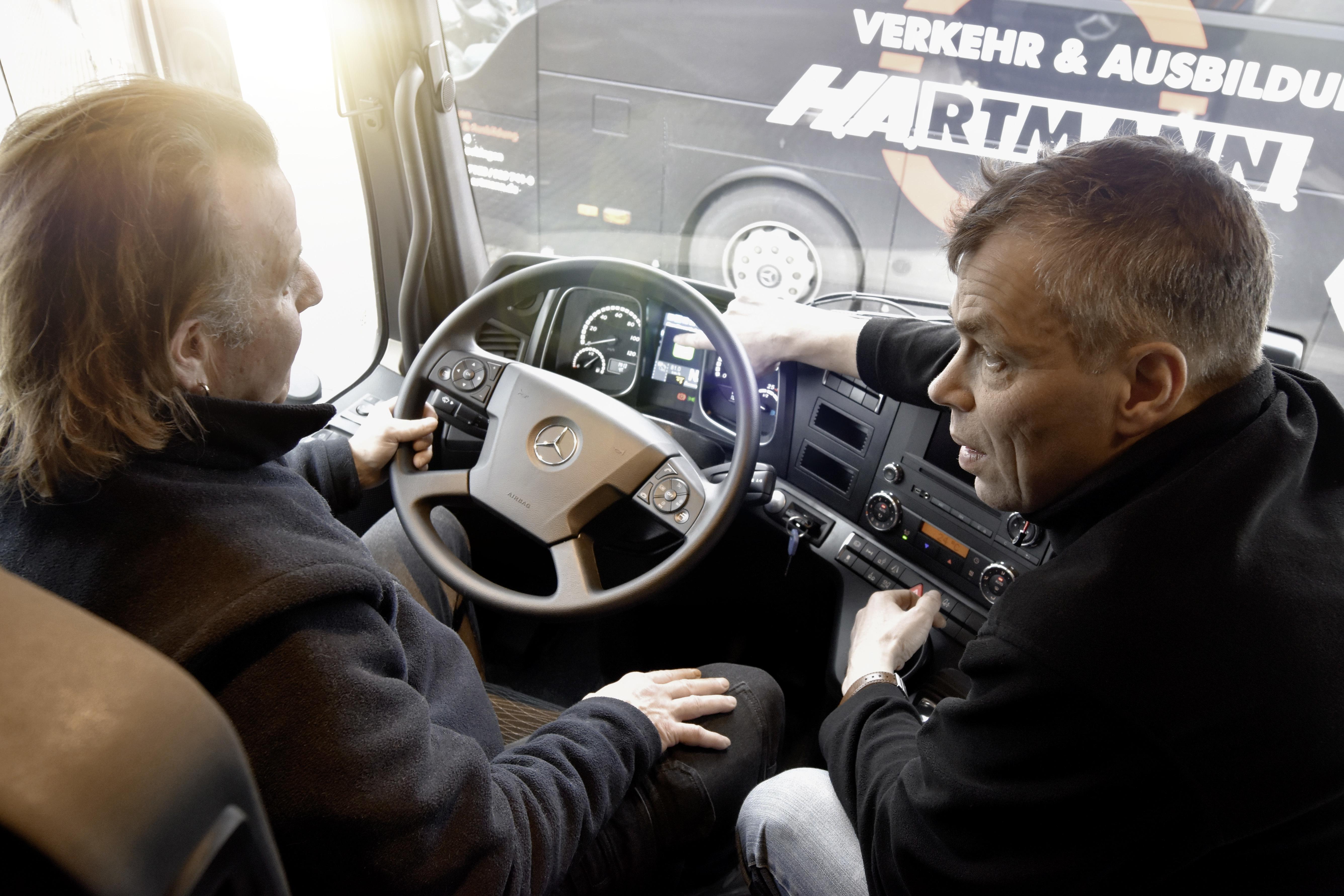 Fahrschulchef Hartmann (rechts) erläutert einem Fahrschüler den neu eingebauten ABA 4 und Abbiege-Assistent.