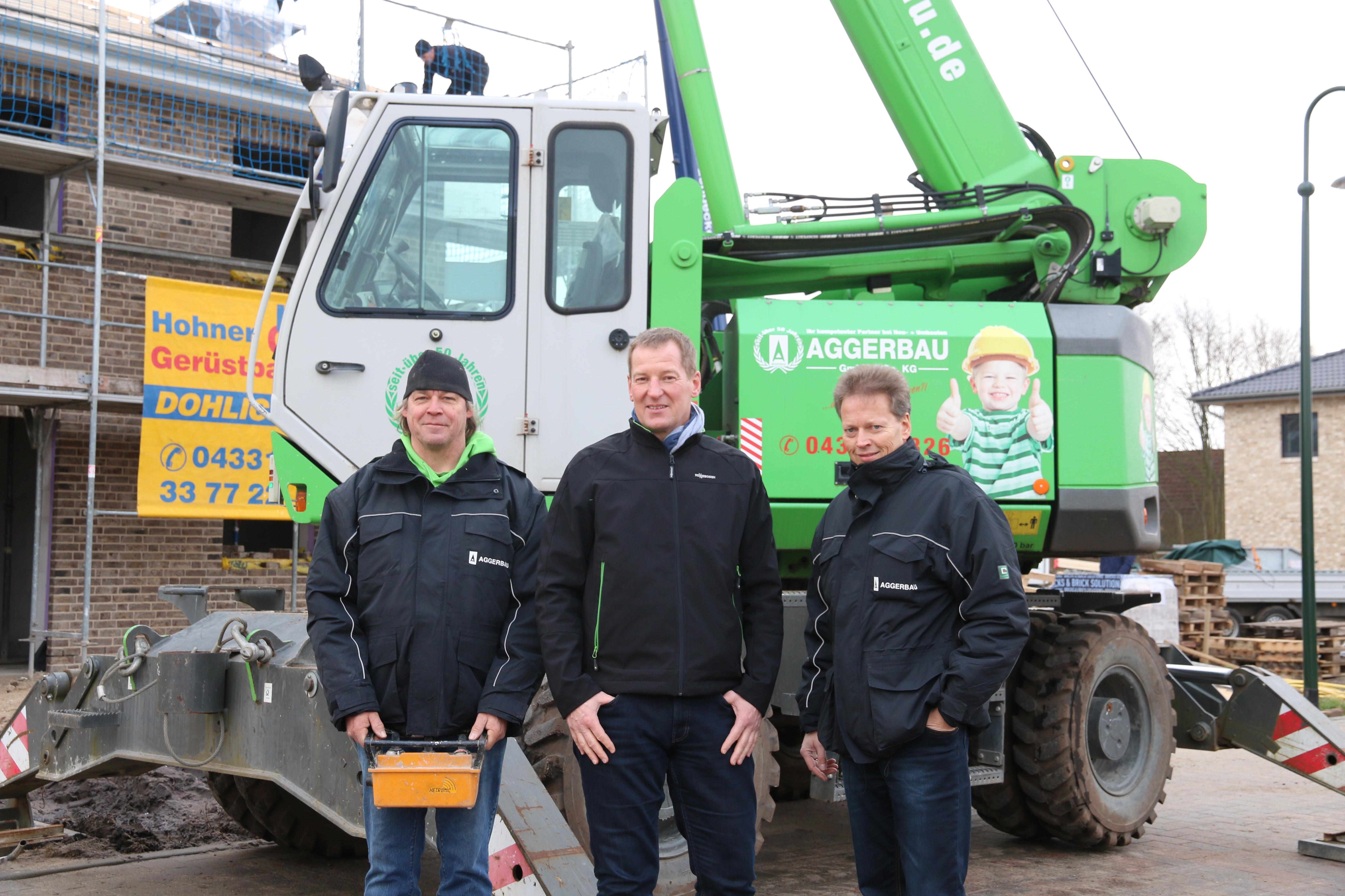 Kranfahrer Peter Koll bedient den 613 stets mit Funkfernsteuerung (links), in der Bildmitte Sven Wegerich vom Vertriebspartner Friedrich Niemann, rechts Jens Agger, Geschäftsführer von Aggerbau.