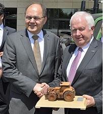 Der Vorsitzende der AGCO/Fendt Geschäftsführung, Peter-Josef Paffen überreicht Bundesminister Christian Schmidt zur Erinnerung ein Traktormodell aus Holz