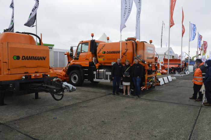 "Frank Schock, Nadine Dammann with distinction ""Unimog ExpertPartner"" and Martin Biesenbach before the U527 with brine sprayer KS5003 on Demopark."