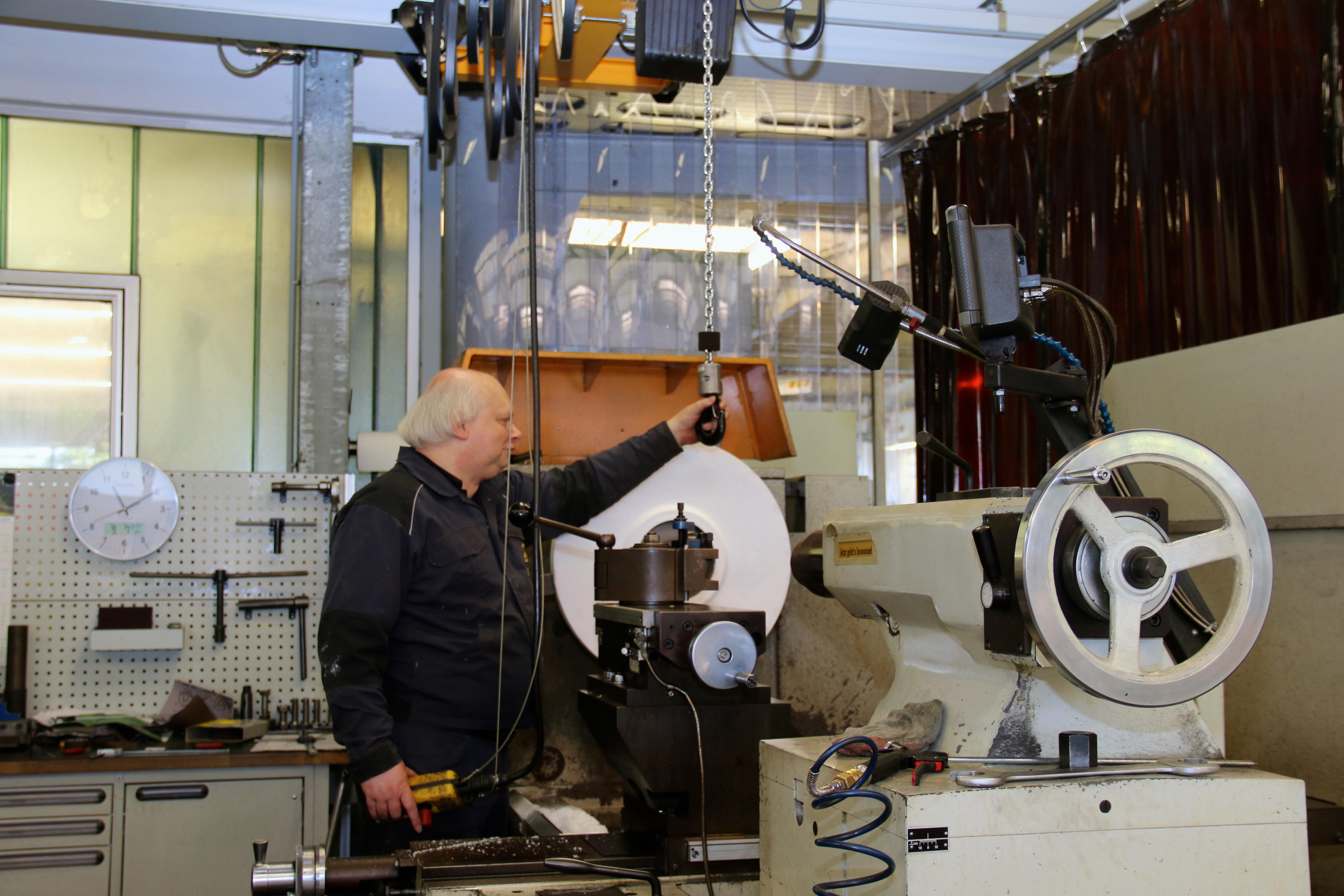 Der Mitarbeiter an der Drehbank bewegt die Teile, die er bearbeiten muss, ergonomisch per Kran